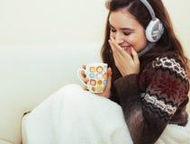 Mulher bonita nova que senta-se na cadeira confortável com café e fotografia de stock