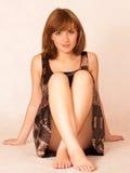 Mulher bonita nova que senta-se no assoalho Imagem de Stock