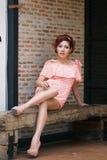 Mulher bonita nova que senta-se no banco de madeira. Foto de Stock