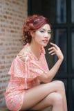 Mulher bonita nova que senta-se no banco de madeira. Imagem de Stock