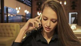 Mulher bonita nova que senta-se no café e que fala no telefone vídeos de arquivo