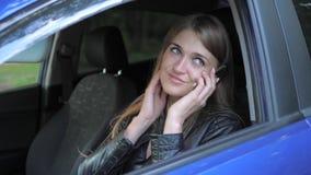 A mulher bonita nova que senta-se no carro e tem o divertimento que fala no telefone video estoque