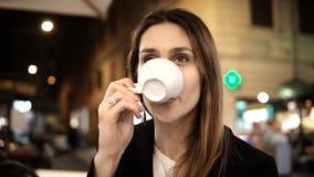 Mulher bonita nova que senta-se no centro de cidade no café, guardando o copo e bebendo o café na noite apenas vídeos de arquivo