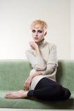 Mulher bonita nova que senta-se no sofá Fotos de Stock