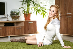 Mulher bonita nova que senta-se no tapete verde em sua sala de visitas Fotografia de Stock Royalty Free