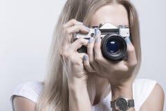 Mulher bonita nova que toma uma foto com uma câmera retro imagens de stock royalty free