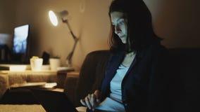 Mulher bonita nova que usa o laptop e surfando os meios sociais que sentam-se no treinador em casa na noite vídeos de arquivo