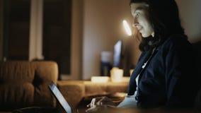 Mulher bonita nova que usa o laptop e surfando os meios sociais que sentam-se no treinador em casa na noite imagem de stock