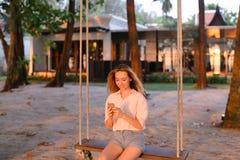 Mulher bonita nova que usa o smartphone e sentando-se no balanço, areia no fundo imagem de stock royalty free