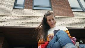 Mulher bonita nova que usa o smartphone perto da constru??o de tijolo vídeos de arquivo
