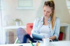 Mulher bonita nova que usa sua tabuleta digital em casa Imagens de Stock Royalty Free