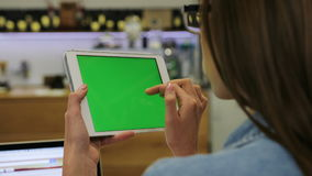 Mulher bonita nova que usa a tabuleta com a tela verde que senta-se no café, imagens do furto Close-up Chave do croma vídeos de arquivo