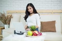 Mulher bonita nova que usa um laptop imagens de stock