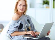 Mulher bonita nova que usa um laptop em casa Imagens de Stock