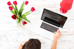 Mulher bonita nova que usa um portátil em casa imagem de stock
