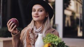 Mulher bonita nova que veste a posição à moda do revestimento na rua que guarda um pacote dos produtos Guarda a maçã vermelha vídeos de arquivo