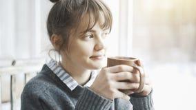 A mulher bonita nova que veste uma camiseta cinzenta está apreciando seu chá em um café e em sonhar acordado Foto de Stock Royalty Free