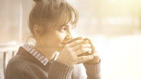 A mulher bonita nova que veste uma camiseta cinzenta está apreciando seu chá em um café e em sonhar acordado alargamento Imagem de Stock