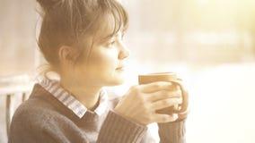A mulher bonita nova que veste uma camiseta cinzenta está apreciando seu chá em um café e em sonhar acordado Imagem tonificada Imagem de Stock Royalty Free