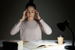 A mulher bonita nova veste o funcionamento ocasional da camisa na noite, tem a dor de cabeça terrível, tenta-a concentrar-se e co foto de stock