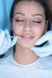 A mulher bonita obtém uma injeção em sua cara Fotografia de Stock Royalty Free