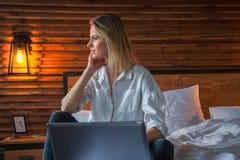 Mulher bonita ocasional feliz que trabalha em um portátil que senta-se na cama na casa foto de stock royalty free