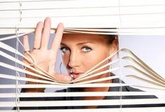A mulher bonita olha através do jalousie Imagem de Stock Royalty Free