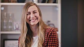 A mulher bonita olha a câmera com pergunta, a seguir sorri felizmente Emoção positiva Cara fêmea consideravelmente caucasiano 4K vídeos de arquivo