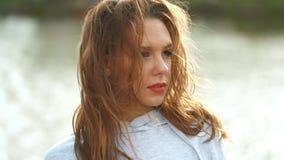 A mulher bonita olha na câmera Seu cabelo encaracolado longo é fundido - acima pelo vento filme