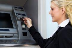A mulher bonita pôs seu cartão de crédito no ATM foto de stock