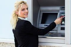 A mulher bonita pôs seu cartão de crédito no ATM Imagens de Stock