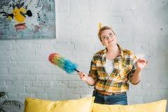 mulher bonita pensativa que levanta com a escova colorida da poeira para limpar imagens de stock