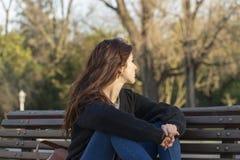 A mulher bonita pensativa reflete no parque e na vista afastado Imagens de Stock Royalty Free
