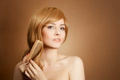 A mulher bonita penteia seu cabelo longo saudável Fotos de Stock Royalty Free