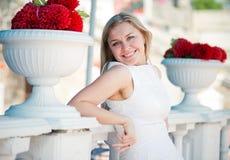Mulher bonita perto das flores vermelhas Foto de Stock
