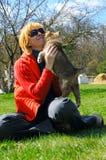 A mulher bonita pets um filhote de cachorro Fotos de Stock Royalty Free