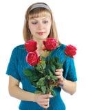A mulher bonita prende o ramalhete de rosas vermelhas foto de stock