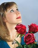 A mulher bonita prende o ramalhete de rosas vermelhas Fotos de Stock Royalty Free