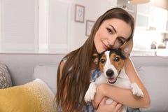 Mulher bonita que abraça seu cão no sofá fotografia de stock