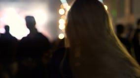 Mulher bonita que acena o cabelo louro e que dança no festival de música, iluminação vídeos de arquivo