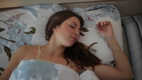 Mulher bonita que acorda em sua cama vídeos de arquivo