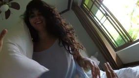 Mulher bonita que acorda o homem que encontra-se na cama em pares novos do pov da manhã no quarto video estoque