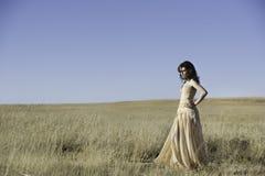 Mulher bonita que anda no campo dourado Foto de Stock Royalty Free