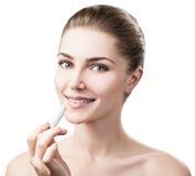 Mulher bonita que aplica o bálsamo de bordo higiênico imagem de stock