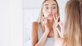 Mulher bonita que aplica o bálsamo de bordo higiênico perto do espelho, a jovem mulher atrativa aplicando o bálsamo e o olhar de  imagem de stock