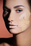 Mulher bonita que aplica o creme fêmea da composição fotografia de stock royalty free