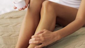 Mulher bonita que aplica o creme a seus pés em casa filme