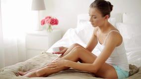 Mulher bonita que aplica o creme a seus pés em casa video estoque