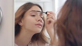 Mulher bonita que aplica o r?mel com a escova nas pestanas no espelho do banheiro video estoque