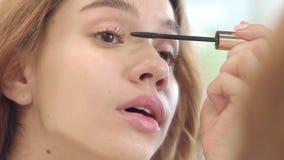 Mulher bonita que aplica o rímel preto para o espelho dianteiro do banheiro das pestanas vídeos de arquivo